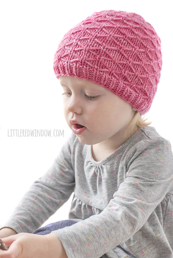 little girl looking off to the left while wearing a gray shirt and bright bubblegum pink knit hat with diamond trellis pattern on it