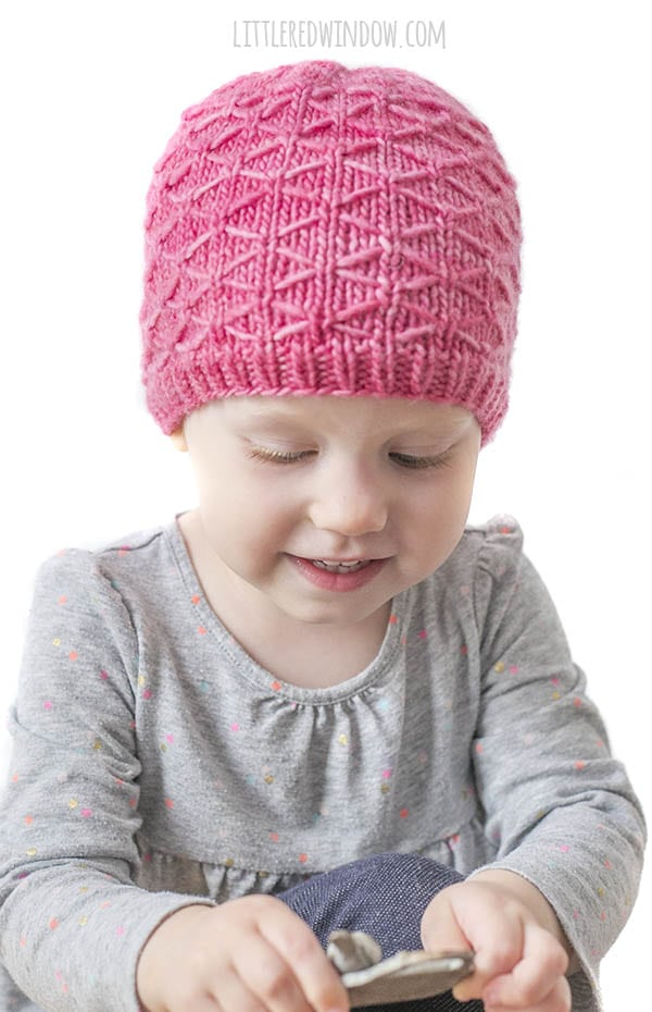 smiling baby looking down at her hands and wearing bright pink trellis hat