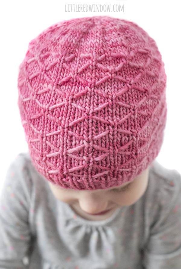 closeup of diamond stitch pattern on bright pink trellis hat knitting pattern