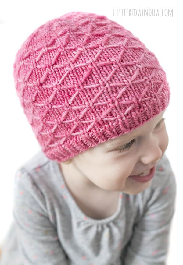 smiling baby leaning forward and looking off to the right while wearing gray shirt and bright pink knit diamond trellis hat