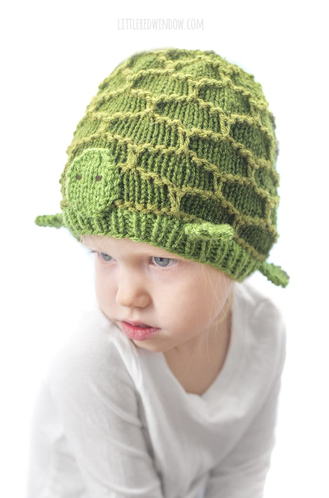 little girl in green turtle hat looking up and to the left
