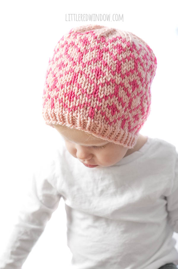 little girl wearing diamond geo hat in light and dark pink looking down at her lap