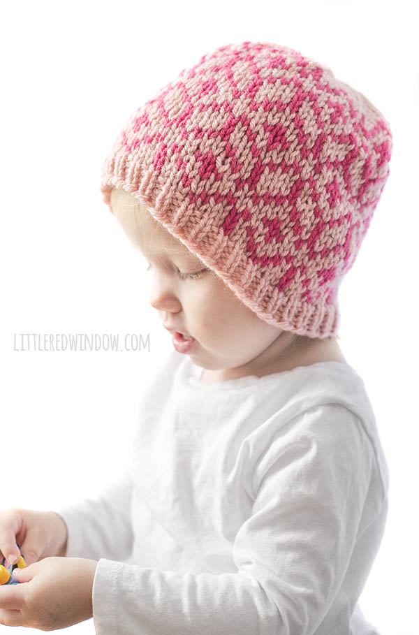 little girl wearing diamond geo hat in light and dark pink looking at something in her hands