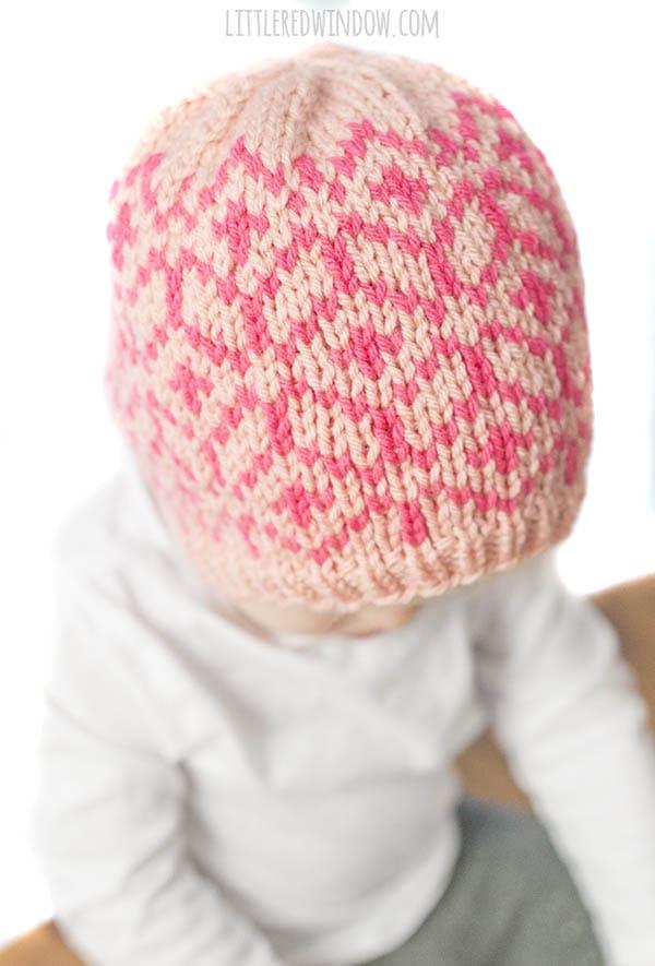closeup of knit geometric fair isle pattern on the diamond geo hat in shades of light and dark pink