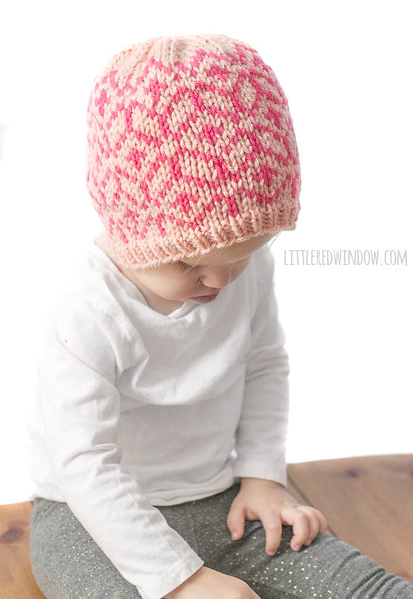 little girl wearing diamond geo hat in light and dark pink sitting on a wood table and looking down at her feet