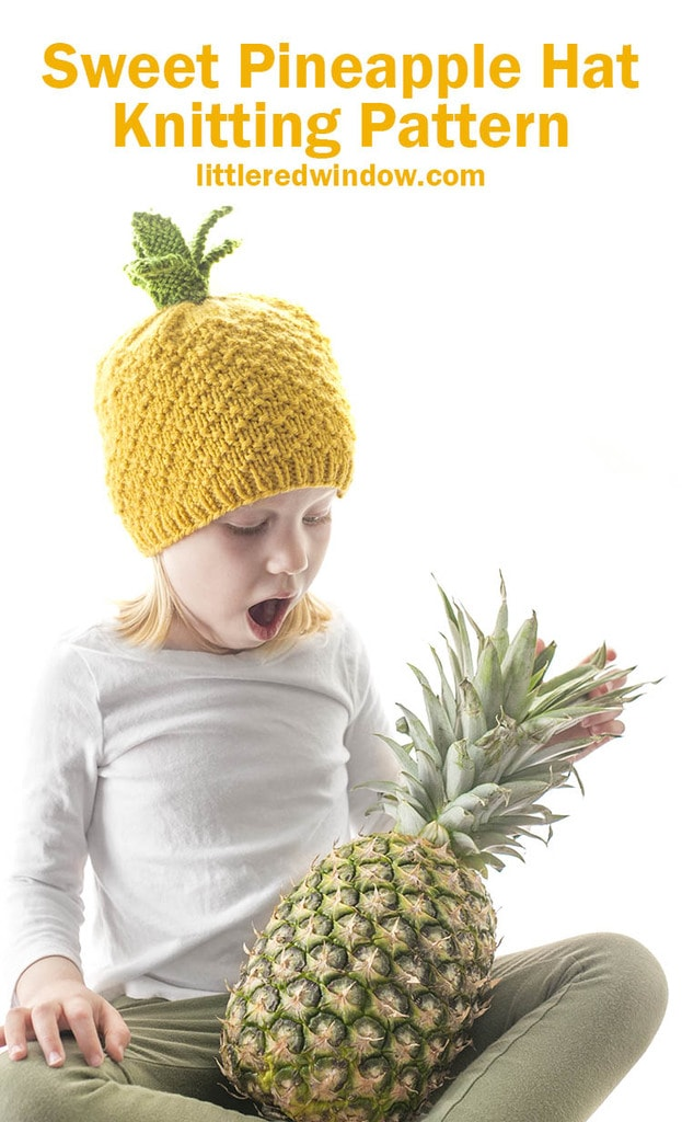 little girl looking down with surprise at a pineapple in her lap while wearing a pineapple knit hat
