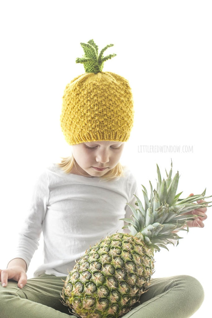 little girl looking down at a pineapple in her lap while wearing a pineapple knit hat