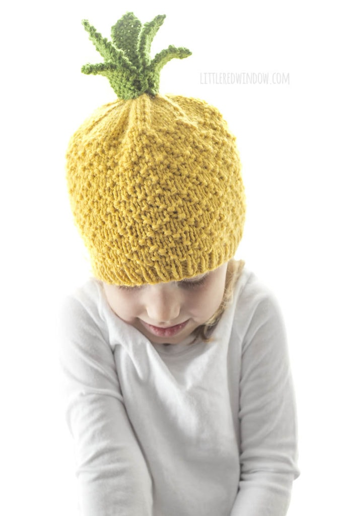 little girl wearing yellow knit pineapple hat with green leaves on top