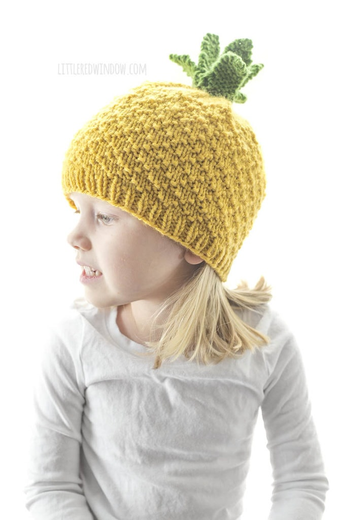 girl in white shirt wearing yellow knit pineapple hat with green leaves on top looking off to the left