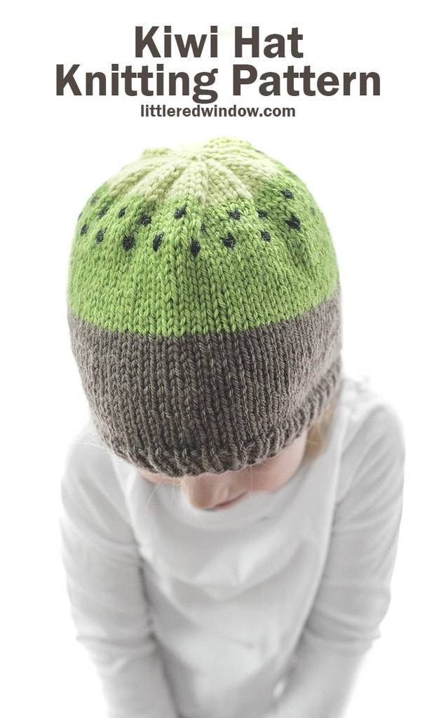 small child modeling brown and green knit kiwi hat knitting pattern with black seeds
