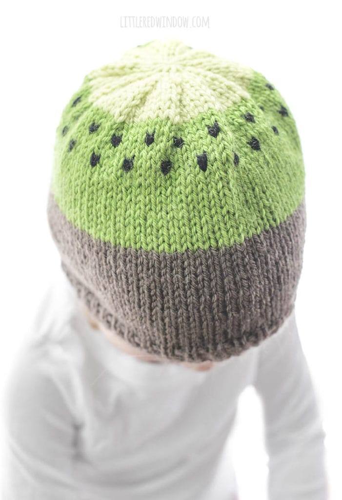 little girl wearing a knit hat that looks like a kiwi fruit and looking down