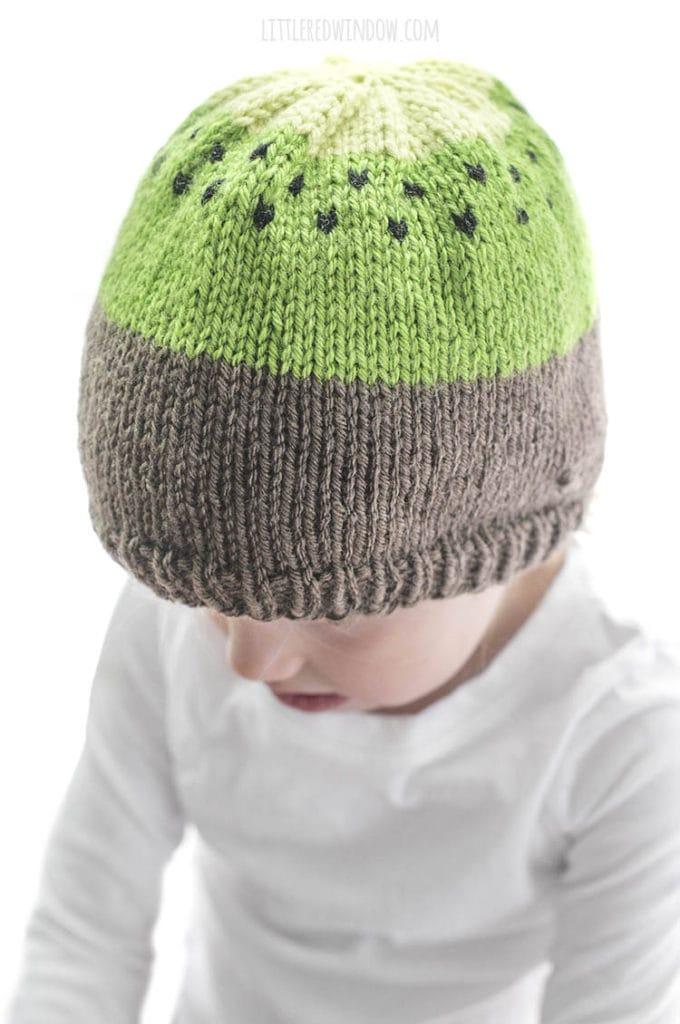 little girl modeling kiwi hat knitting pattern and wearing a white shirt