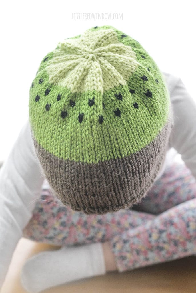 top view of small child wearing kiwi hat knitting pattern and leaning forward