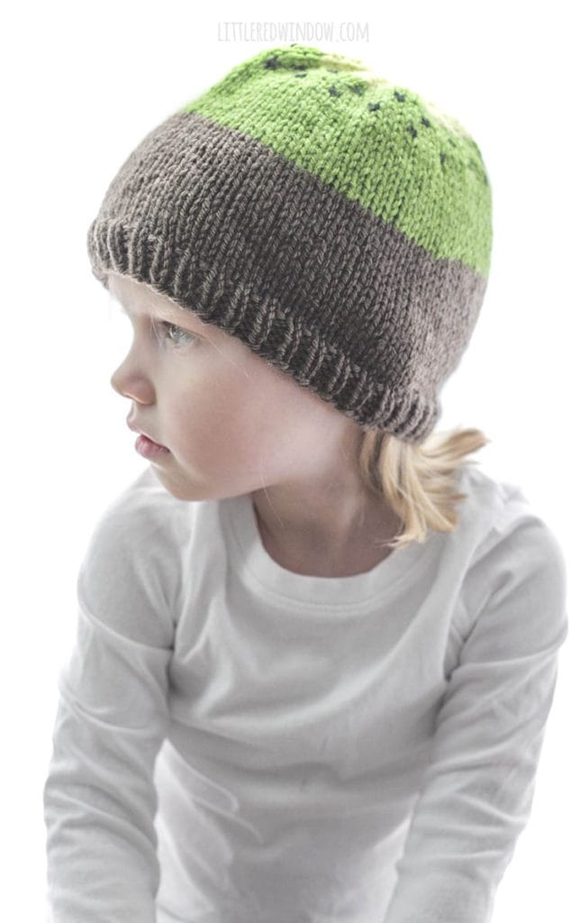 girl wearing knit kiwi hat for babies and looking off to the left