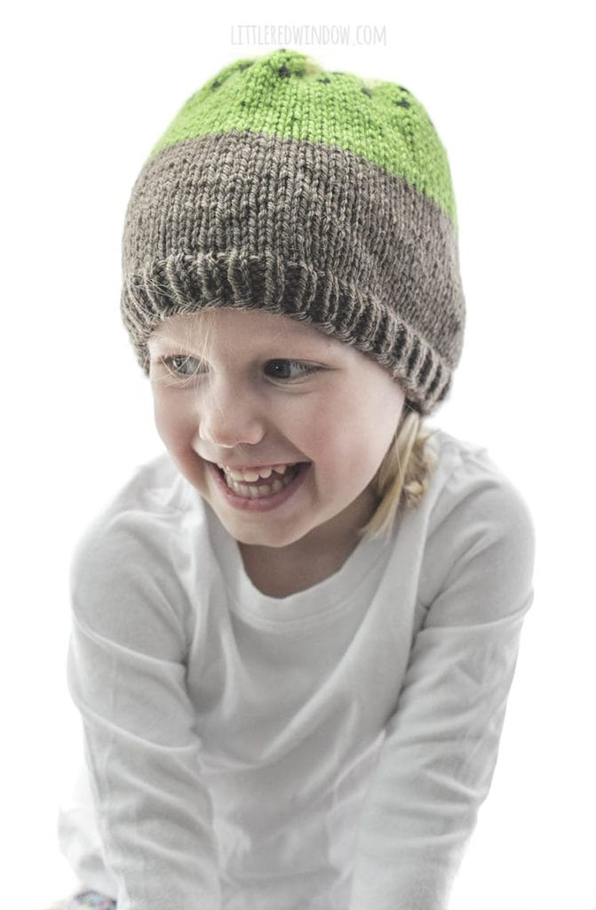 laughing girl wearing a white shirt and brown and green knit kiwi hat