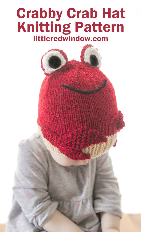 little girl in gray shirt wearing a red knit hat that looks like a red crab looking down at her lap