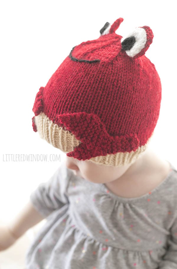 side view of baby girl in gray shirt wearing a red crab hat
