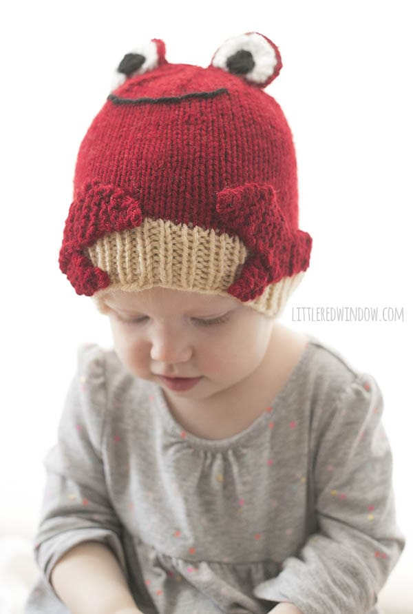little girl in red crab hat looking down at something in her hands