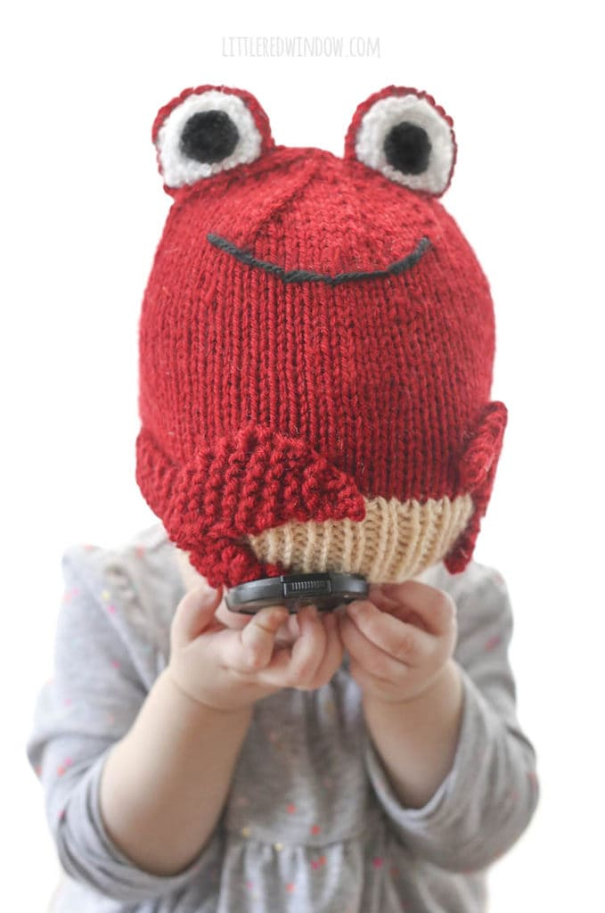 little girl in gray shirt wearing a red knit hat that looks like a crab and covering her face with her hands