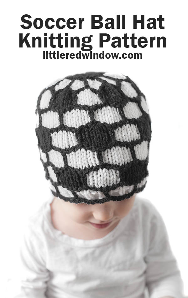 little girl in white shirt wearing a black and white soccer ball hat and looking down at her lap