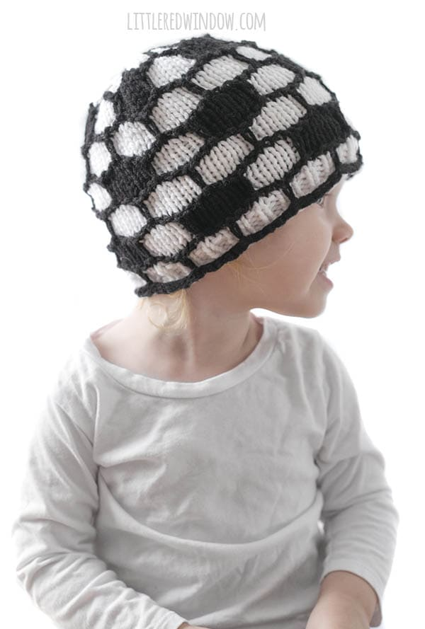 little girl in white shirt wearing black and white soccer ball hat and looking off to the right
