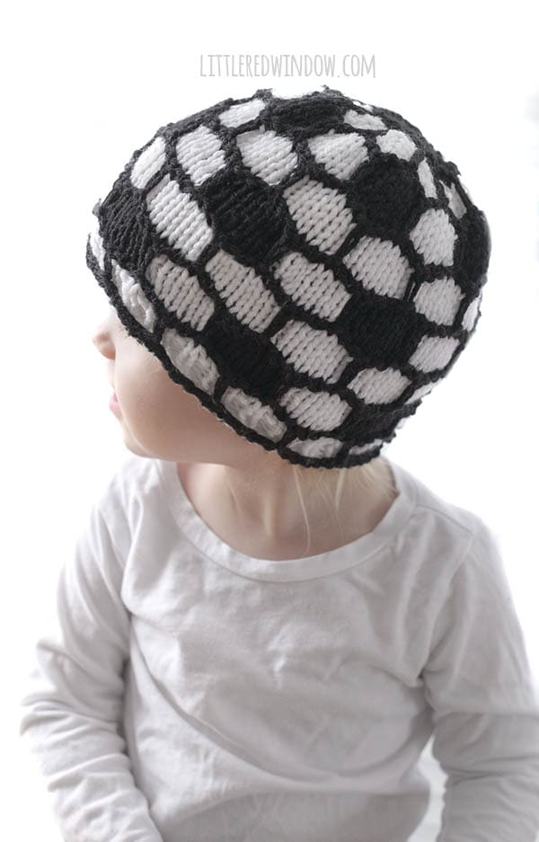 little girl in white shirt wearing black and white soccer ball hat and looking off to the left