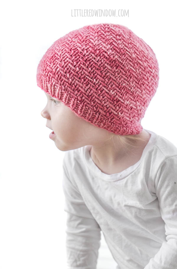 girl in white shirt wearing bubblegum pink knit hat with diagonal weave knit pattern on it looking off to the left