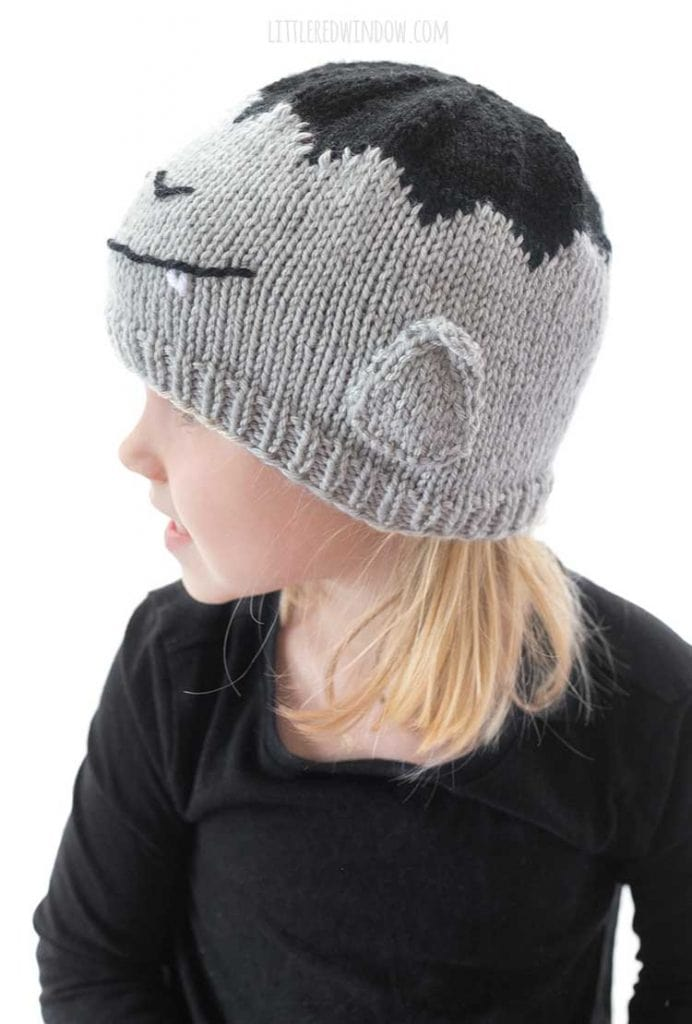 side view of girl wearing vampire hat with pointy ears on the side of it