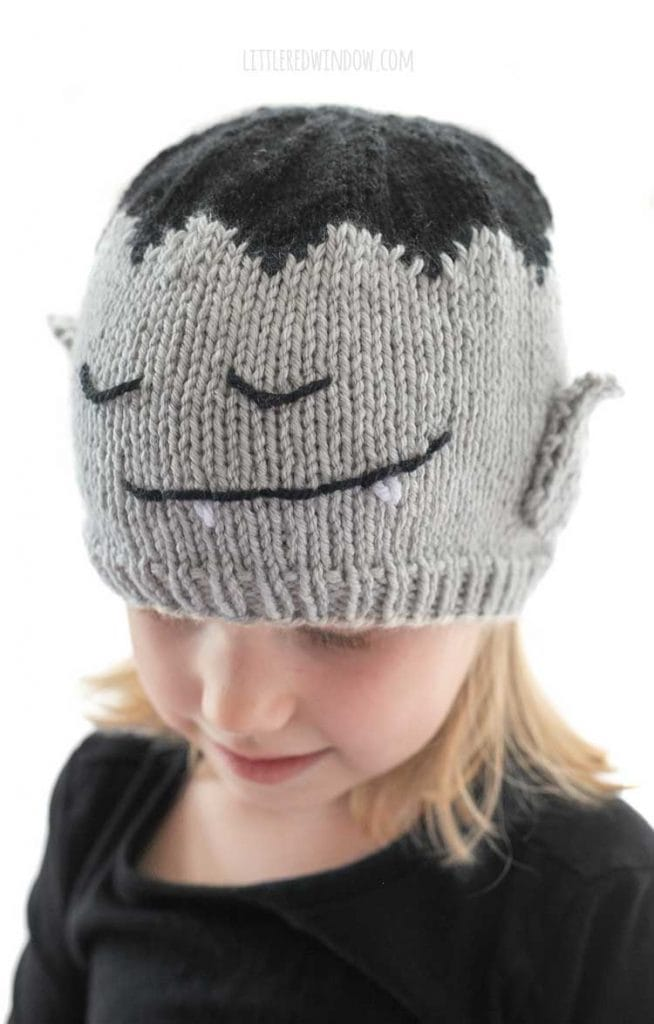 closeup of the face on the vampire hat with closed eyes and a smile with pointy white vampire teeth embroidered