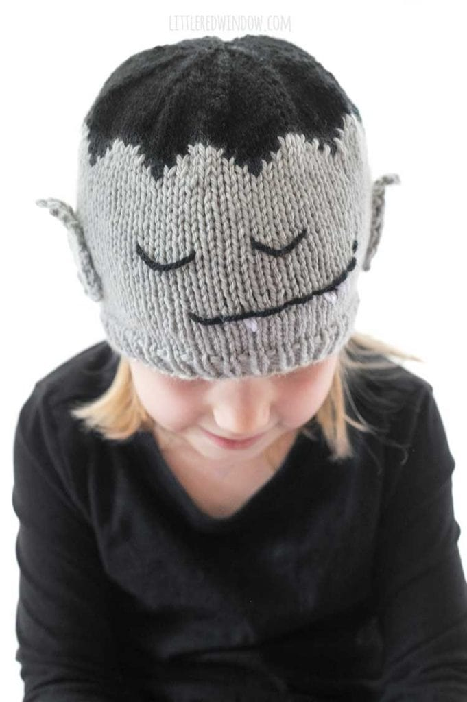 front view of girl wearing vampire hat that has a cute knit vampire face on the front and pointy vampire ears on the sides