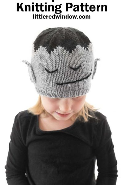 little girl in black shirt wearing gray and black knit hat with a vampire face on it