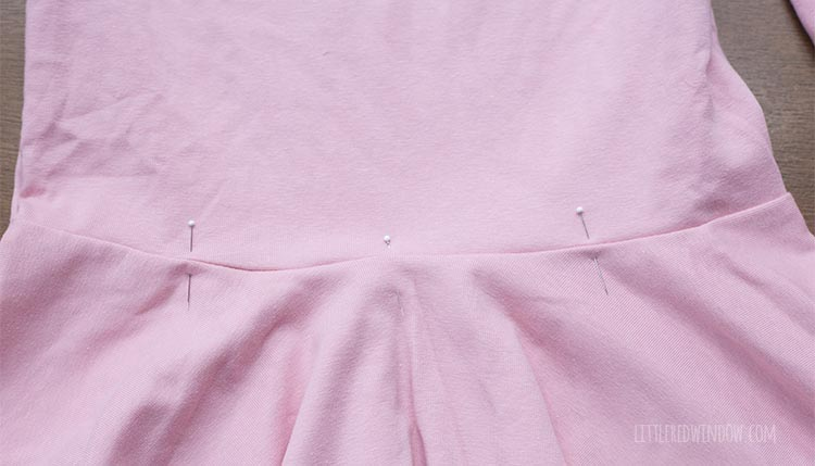 pink dress  that will be a birthday cake costume with evenly spaced pins around the waist