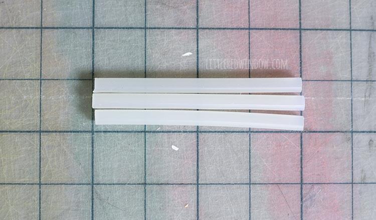 3 four inch long white mini hot glue sticks on a gridded cutting mat