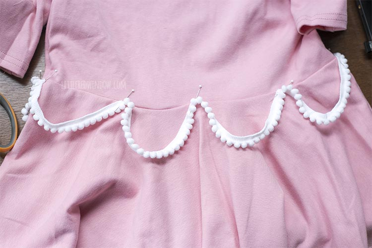 pink dress with pink pom pom trim swagged around the waist to look like frosting on a birthday cake costume