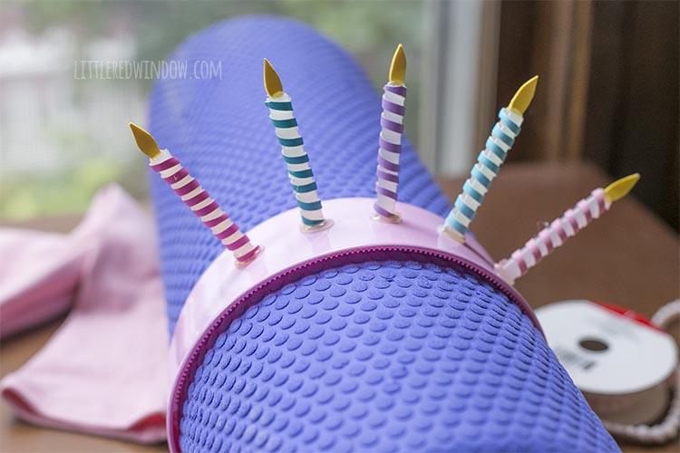 6 hot glue stick candles attached to the top of a pink plastic headband which is held by a purple foam roller finished headpiece for the birthday cake costume