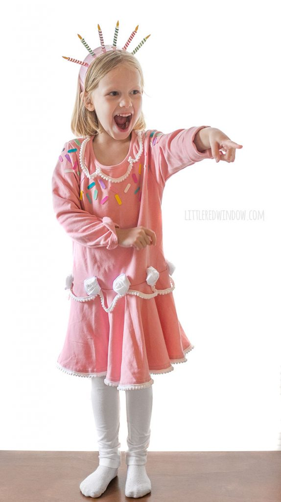 girl in pink birthday cake costume looking surprised and pointing off to the right