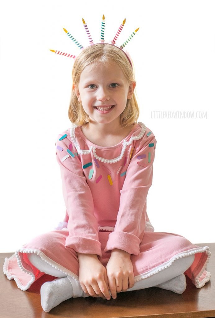 little girl in pink birthday cake costume sitting cross legged and smiling at the camera