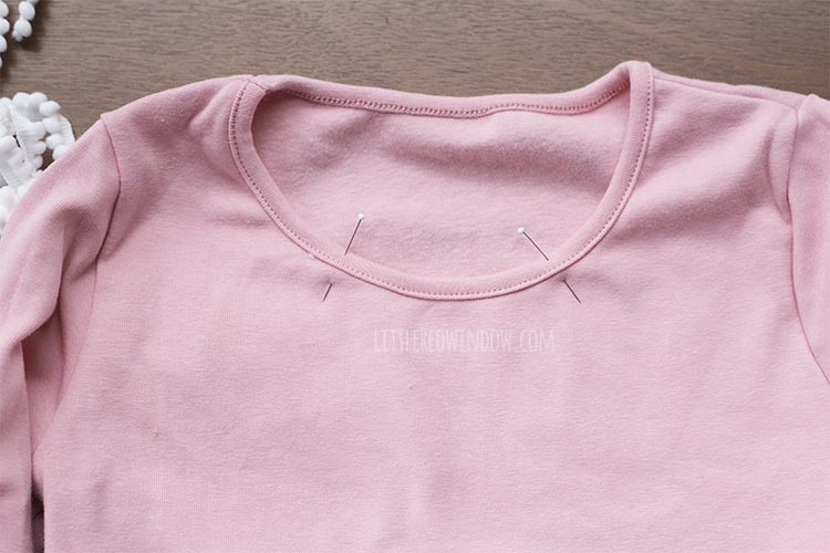 neckline of pink dress with evenly spaced pins