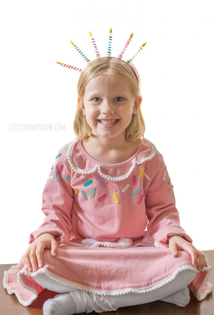 girl casually sitting on a table wearing a pink birthday cake costume with a candle headband