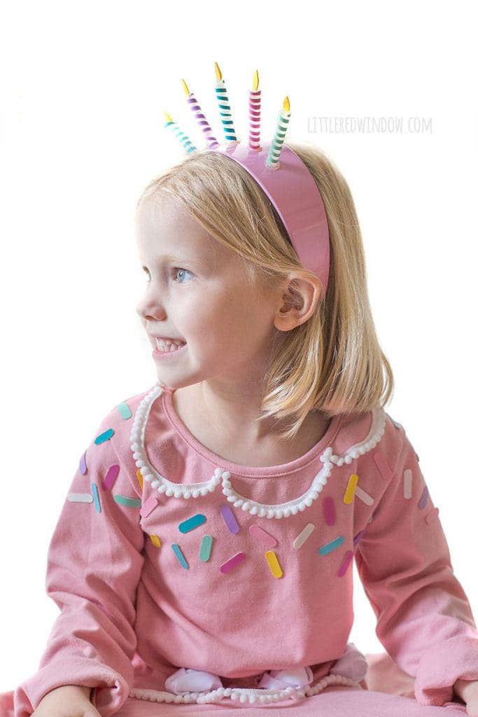 closeup of girl in pink birthday cake costume with birthday candle headband smiling and looking off to the left