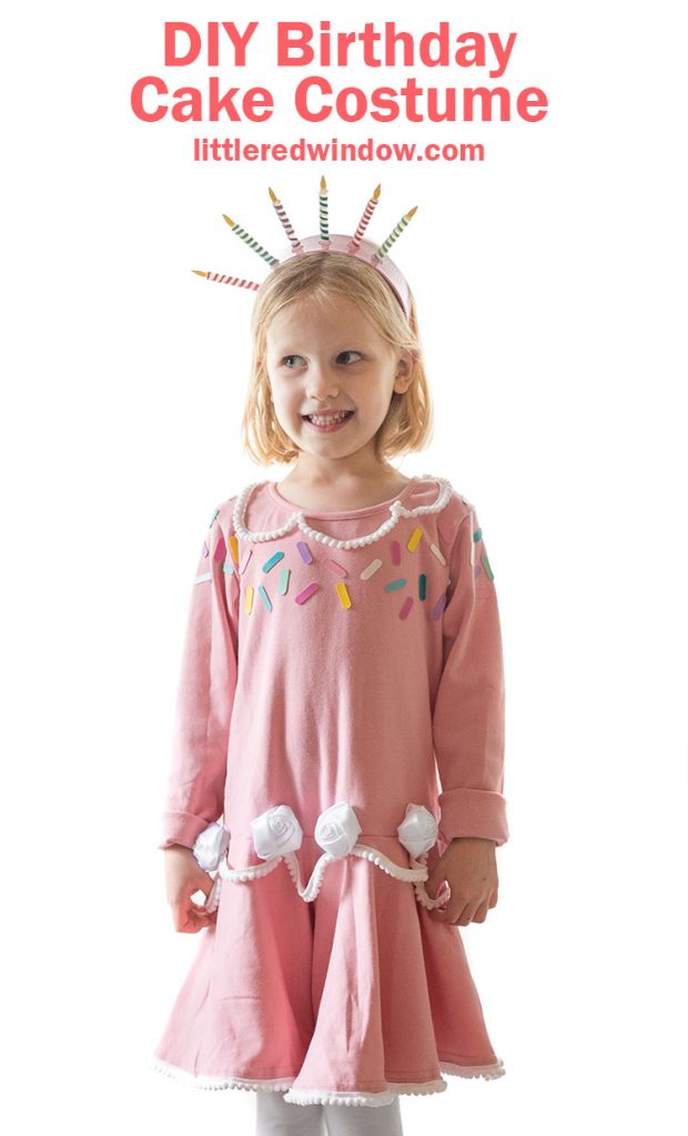girl in pink birthday cake dress with sprinkles and white frosting rosettes smiling and standing on a table