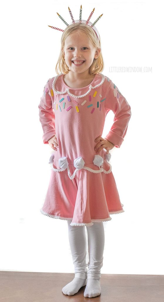 smiling girl in pink birthday cake dress with white leggings standing on a table with her hands on her hips.