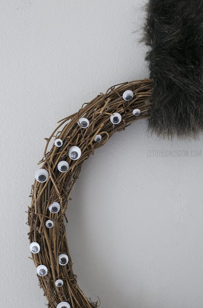 closeup of one quarter of creepy googly eyes wreath with faux fur hanging strip
