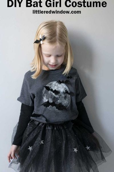 little girl in gray shirt with full moon and bats on it