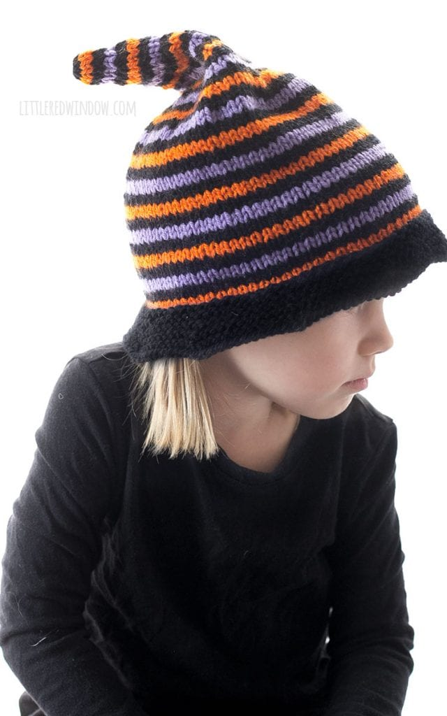 little girl wearing knit halloween witch hat with orange black and purple stripes and looking down and to the right